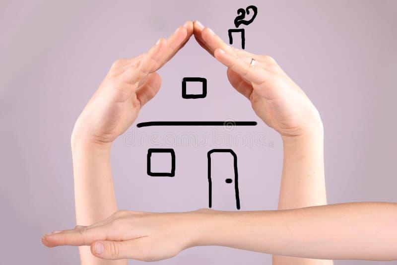 Händer som gör Shape av ett hus på Gray Background arkivfoto
