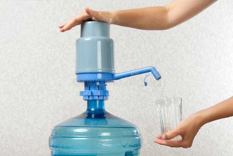Händer som häller vatten in i exponeringsglas från flaskan med en pump royaltyfri bild