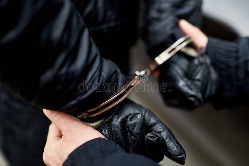 Händer som handfängslas bak tillbaka arkivbilder