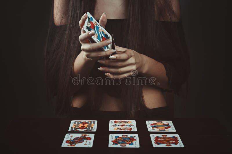 Händer som hasar tarokkort arkivbild