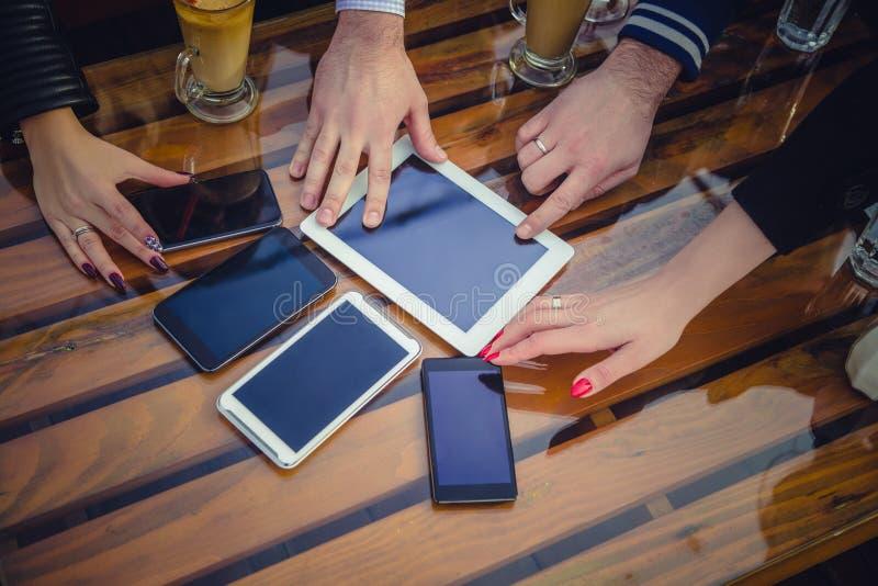 Händer som når för mobiltelefoner och minnestavla royaltyfri fotografi