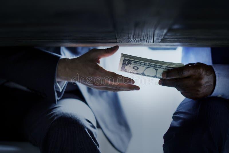 Händer som passerar pengar under tabellkorruptionbestickning royaltyfria foton