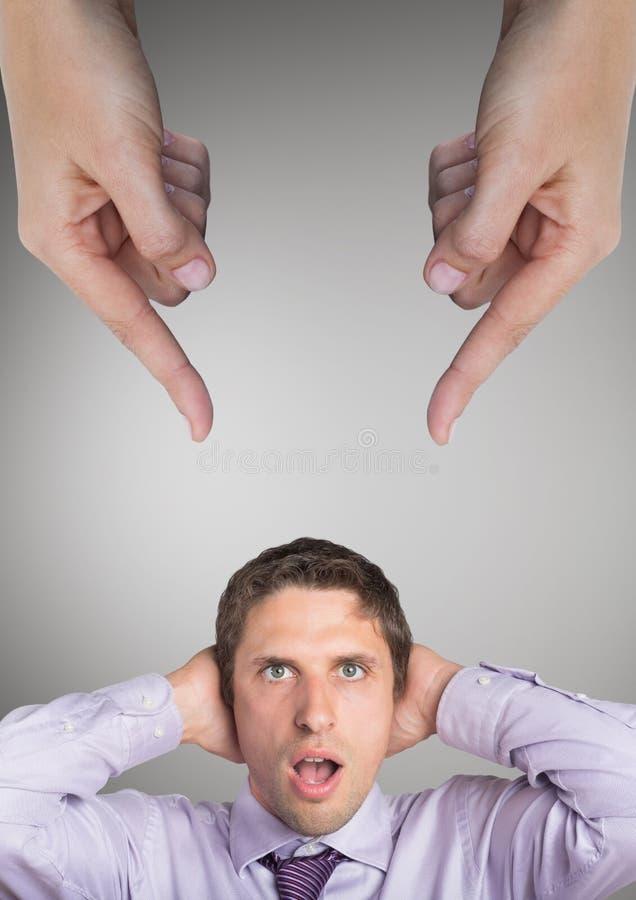 Händer som pekar på den förvånade affärsmannen mot grå bakgrund arkivbild