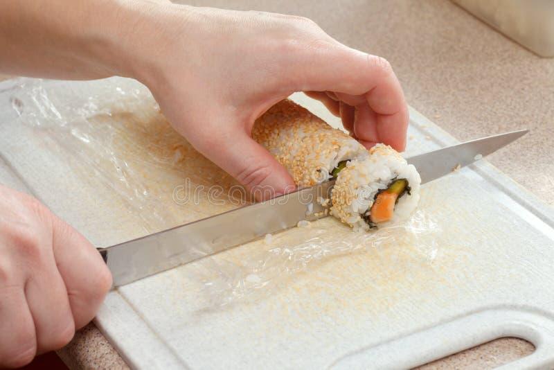 Händer som rullar sushi Kock skivade sushirullar royaltyfria foton