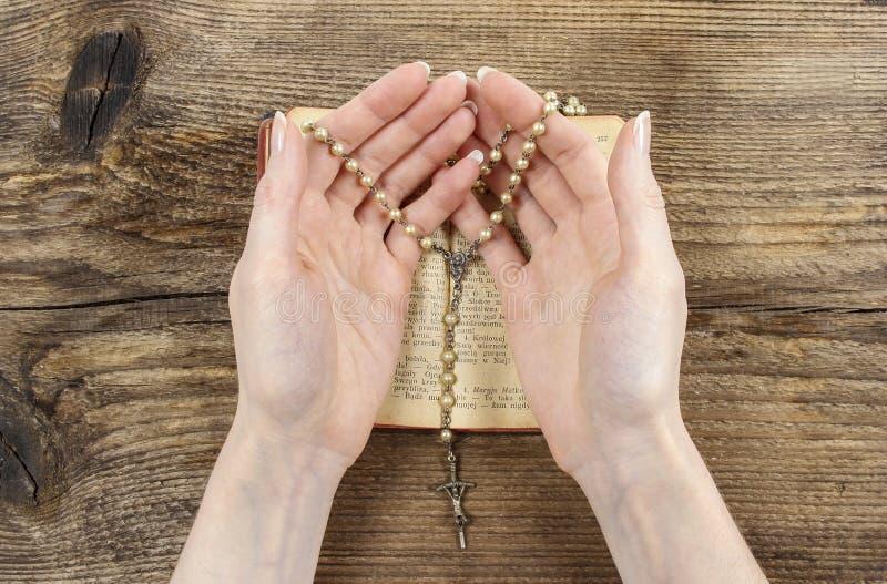 Händer som rymmer bibeln och ber med en radband fotografering för bildbyråer