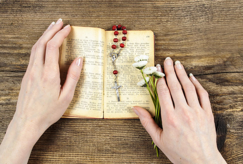 Händer som rymmer bibeln och ber med en radband arkivfoton