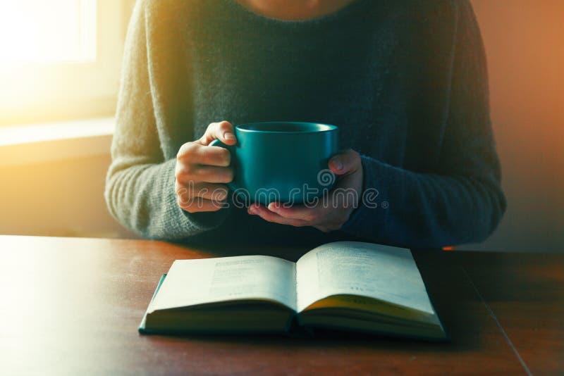 Händer som rymmer boken och läsning med kaffe arkivbilder