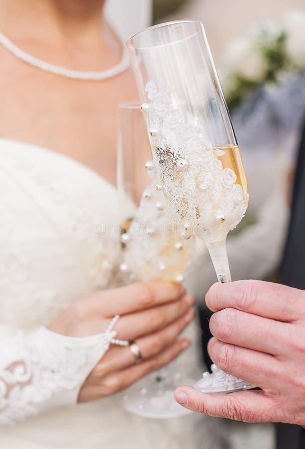Händer som rymmer bröllopchampagneexponeringsglas royaltyfria bilder