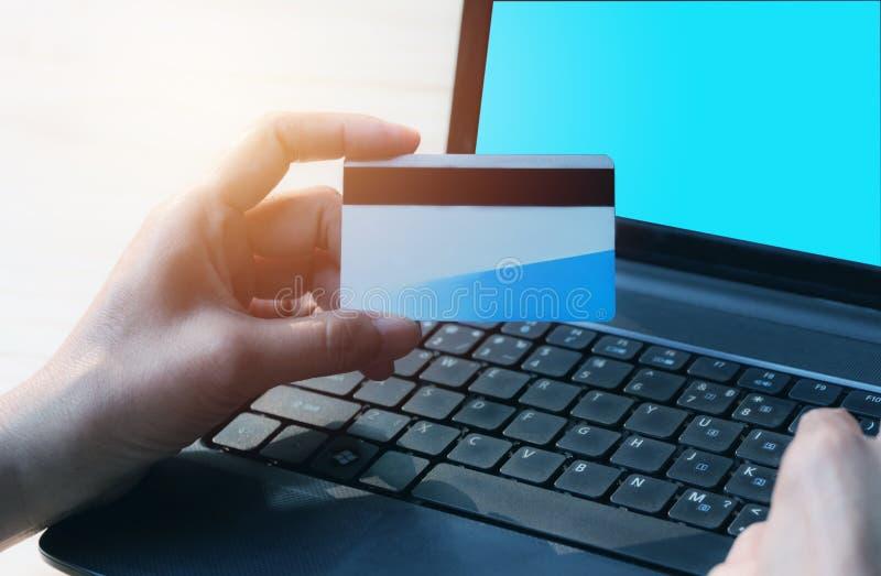 Händer som rymmer den blåa kreditkorten och använder en bärbar dator för online-sho royaltyfria bilder