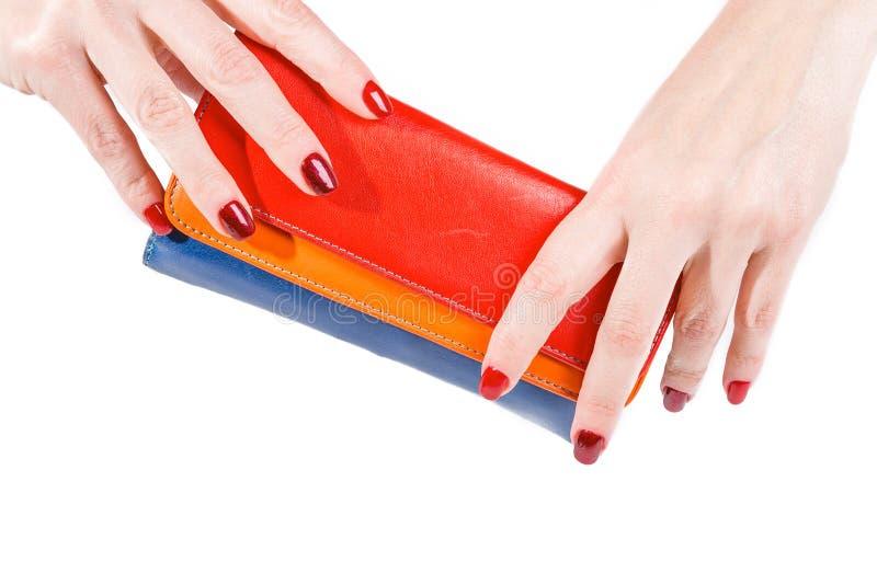 Händer som rymmer den flerfärgade plånboken som isoleras på vit bakgrund royaltyfri bild