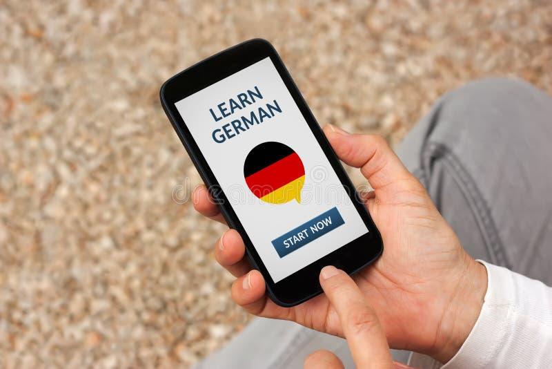 Händer som rymmer den smarta telefonen med, lär tyskt begrepp på skärmen fotografering för bildbyråer