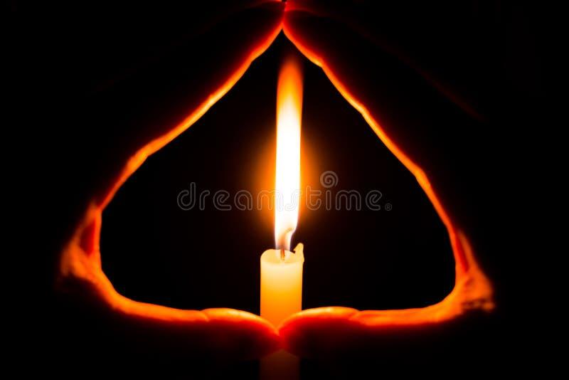 Händer som rymmer en brinnande stearinljus i mörker arkivbilder