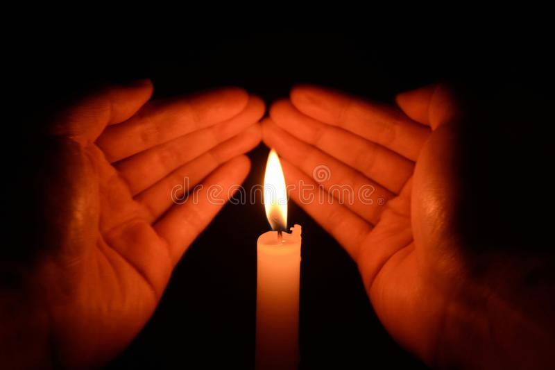 Händer som rymmer en brinnande stearinljus i mörker arkivfoton