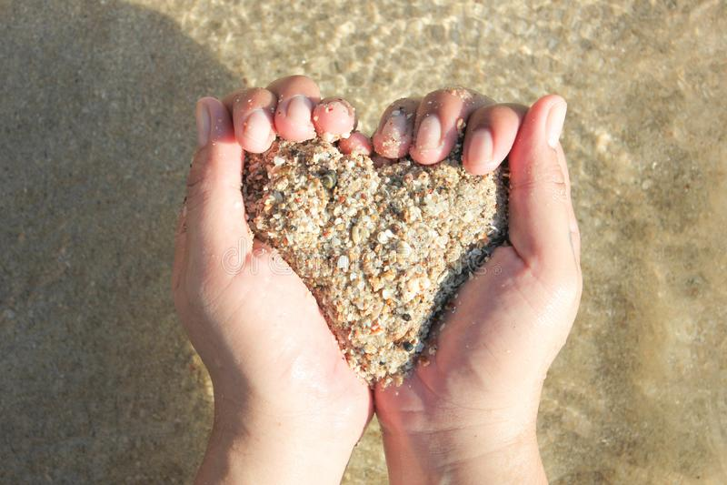 Händer som rymmer en sand i formen av hjärtan arkivbild