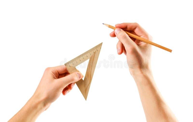 Händer som rymmer en triangulär linjal och blyertspenna på en vit backgroun royaltyfri fotografi