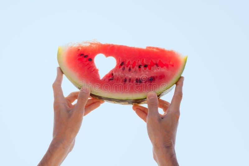 Händer som rymmer en vattenmelonskiva med hjärtamitten in mot himlen royaltyfri fotografi