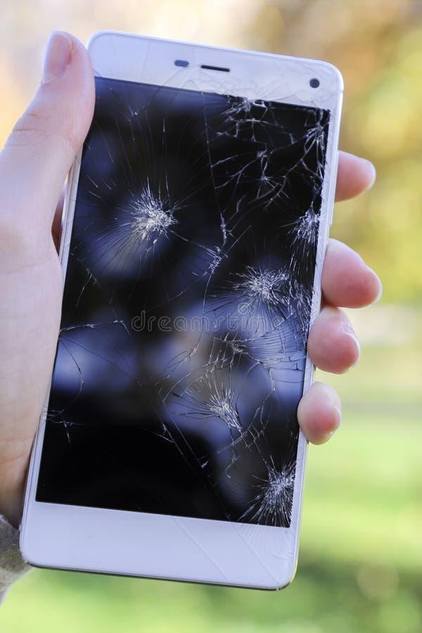 Händer som rymmer ett brutet, ilar telefonen arkivfoto