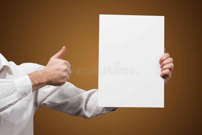 Händer som rymmer ett vitbokmellanrum isolerat på brun bakgrund royaltyfri fotografi