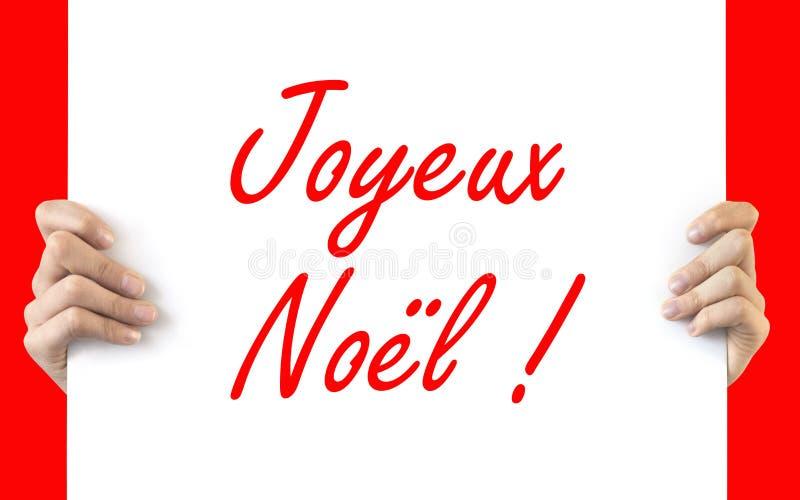 Händer som rymmer ett vitt bräde Joyeux Noel fotografering för bildbyråer