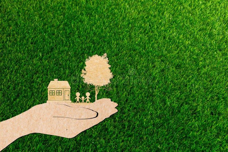 Händer som rymmer hem- stamträd- och bilgräsbakgrund royaltyfri fotografi