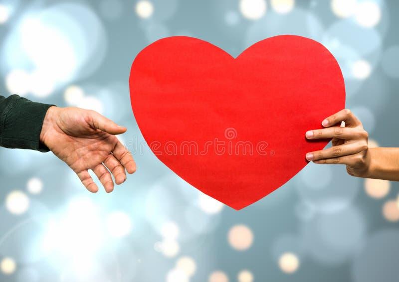Händer som rymmer hjärta med mousserande ljus bokehbakgrund royaltyfri foto