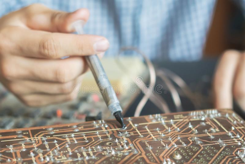 Händer som rymmer injektionsspruta- och reparationsdatorbrädechip f arkivfoto