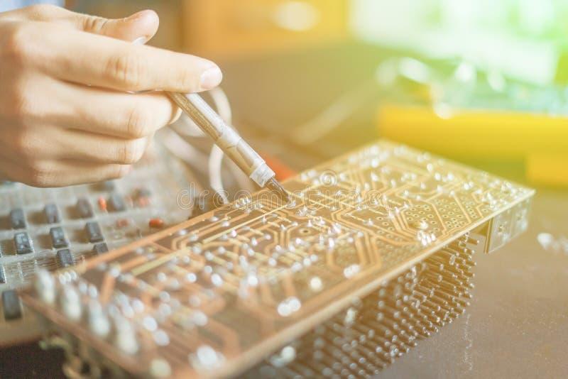 Händer som rymmer injektionsspruta- och reparationsdatorbrädechip f royaltyfri fotografi