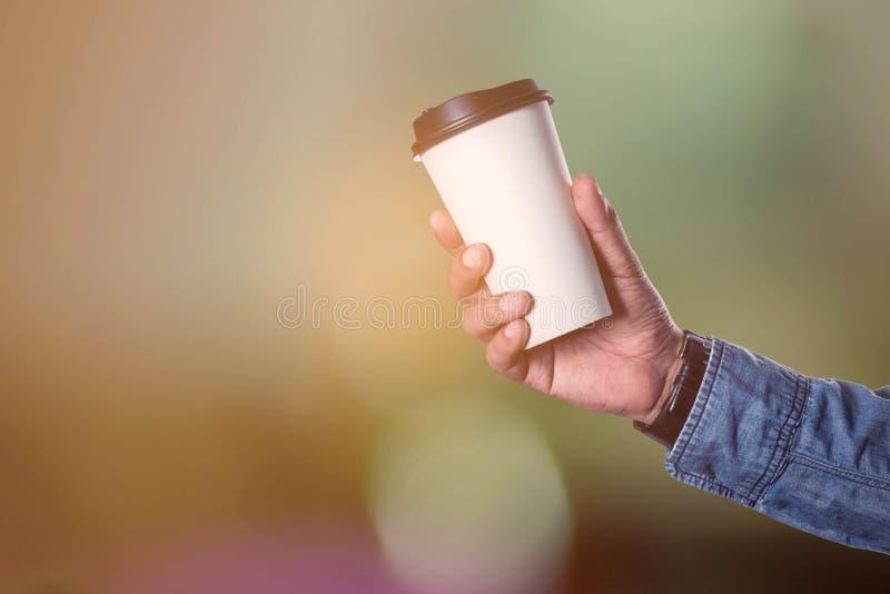 Händer som rymmer kaffekoppen royaltyfri bild