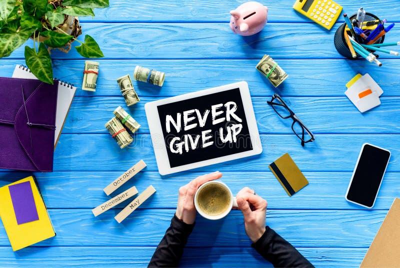 Händer som rymmer kaffekoppen på den blåa trätabellen vid pengar och den digitala minnestavlan, ger upp aldrig inspiration royaltyfria foton