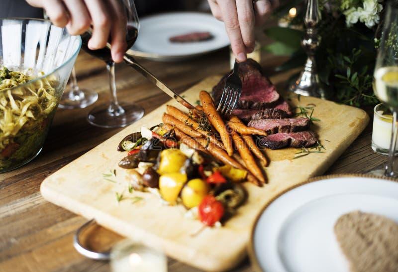 Händer som rymmer kniven och gaffeln som får mat från maträtt arkivfoto