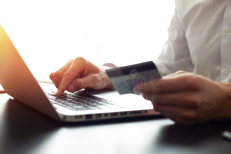 Händer som rymmer kreditkorten och använder bärbara datorn card grund shopping för dof-fokushanden online mycket arkivbilder