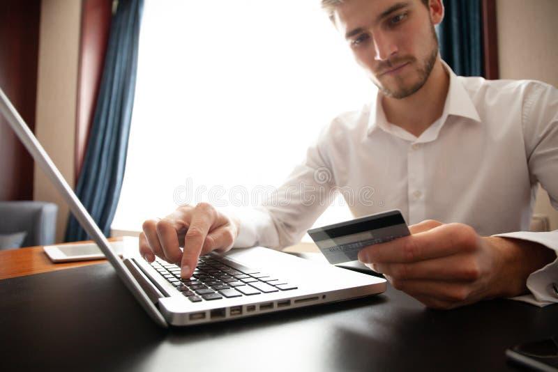 Händer som rymmer kreditkorten och använder bärbara datorn card grund shopping för dof-fokushanden online mycket royaltyfri fotografi