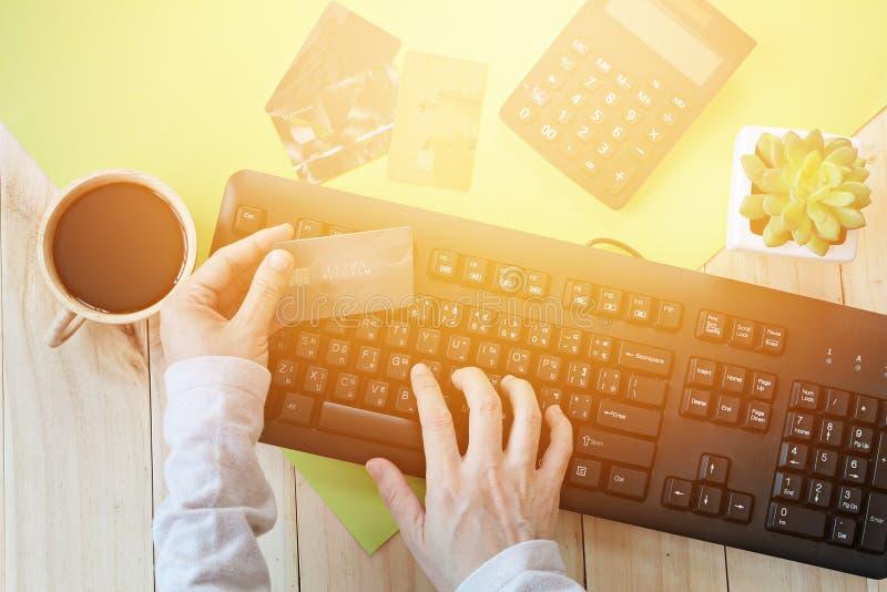 Händer som rymmer kreditkorten och använder datoren för on-line royaltyfri bild