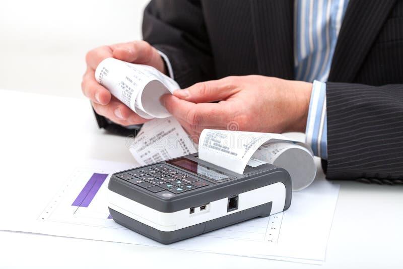 Händer som rymmer kvittot från kassaapparaten royaltyfri foto