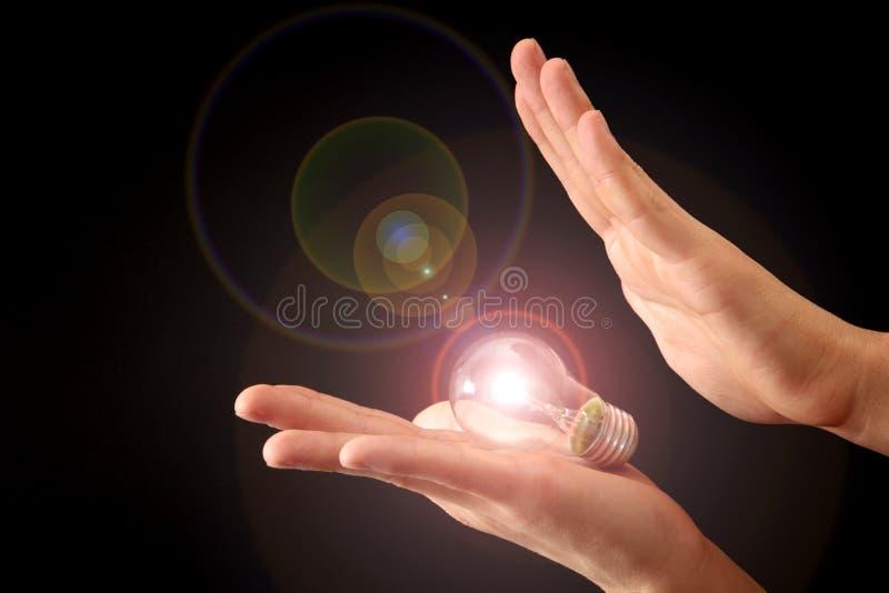 händer som rymmer lampan som skiner royaltyfri fotografi
