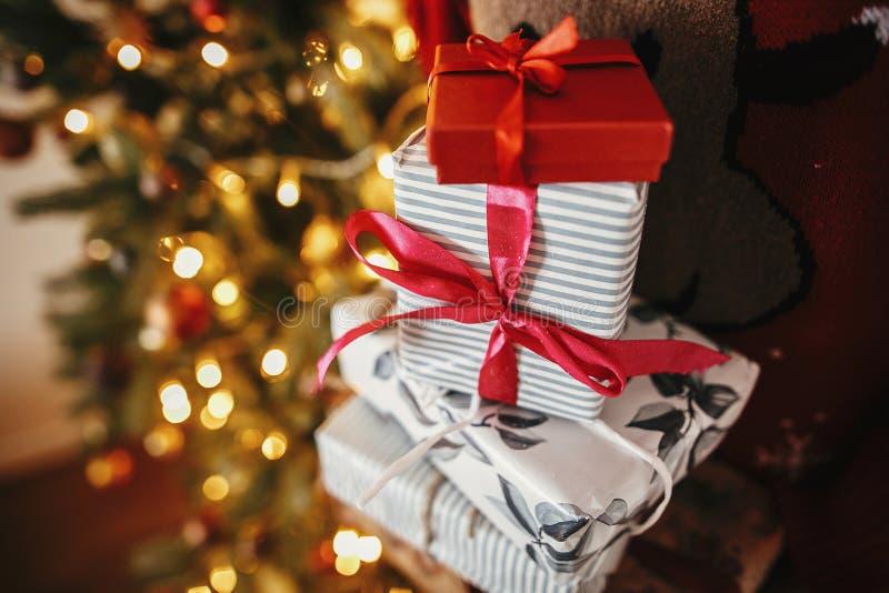 Händer som rymmer många julgåvaaskar på den guld- härliga chrien royaltyfria bilder