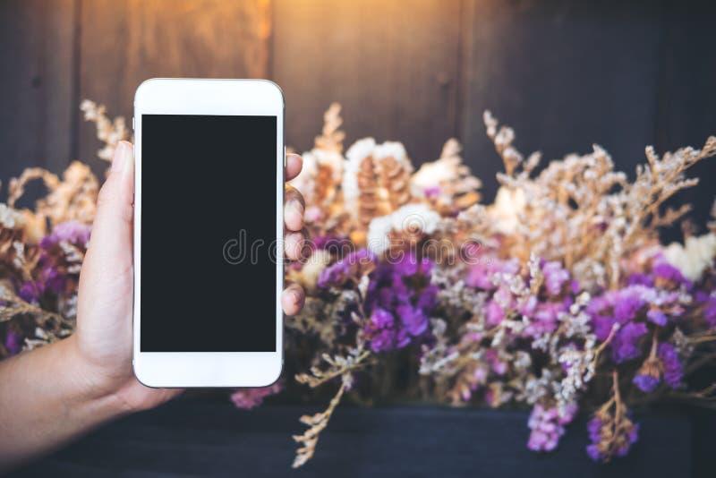 Händer som rymmer och visar den vita mobiltelefonen med mellanrumssvartskärmen med färgrikt, torkar blommor och träväggbakgrund i fotografering för bildbyråer