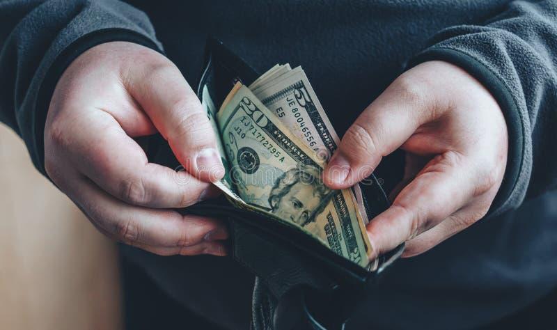 Händer som rymmer oss dollarräkningar och öppen plånbok eller påse räkna manpengar arkivfoto
