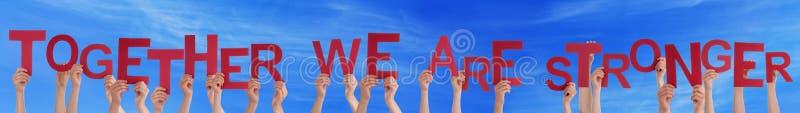 Händer som rymmer rakt ord tillsammans är vi, starkare blå himmel royaltyfria bilder
