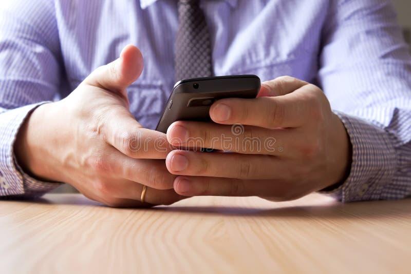 Händer som rymmer smartphonen royaltyfri fotografi