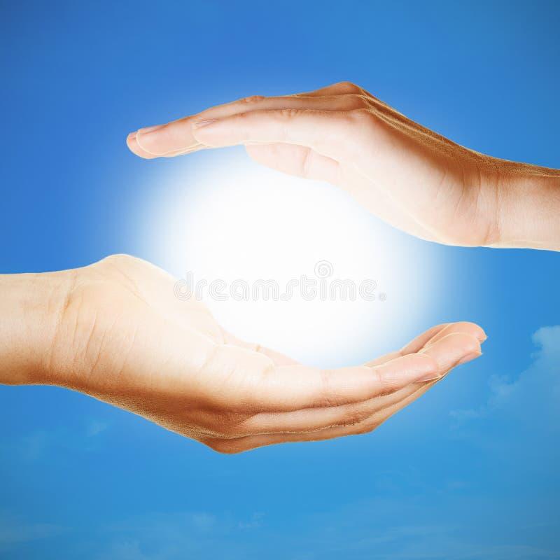 Händer som rymmer solen som meditationbegrepp arkivfoto