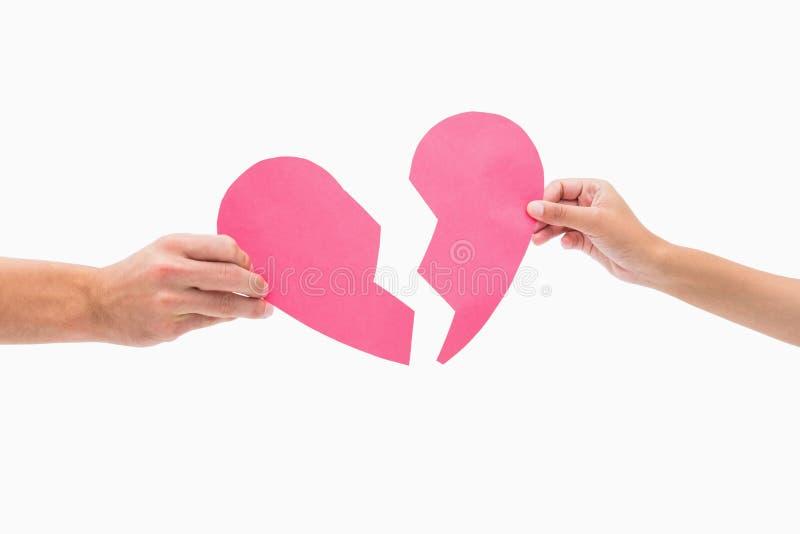 Händer som rymmer två halvor av bruten hjärta royaltyfria foton