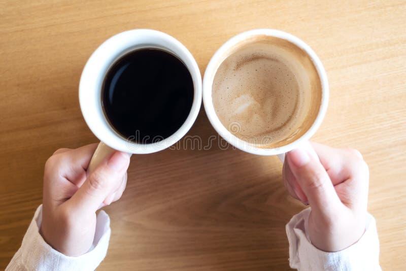 Händer som rymmer två vita koppar kaffe på trätabellen i kafé arkivbild