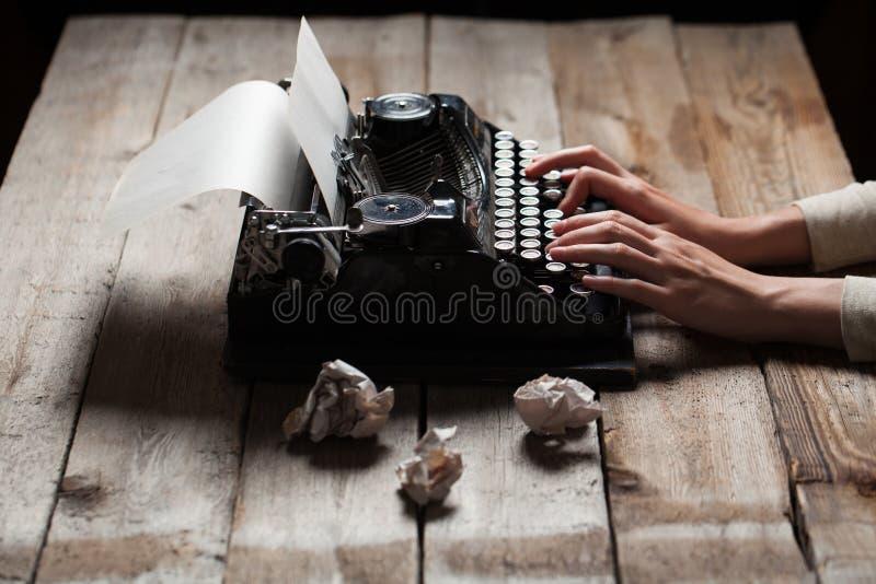 Händer som skriver på den gamla skrivmaskinen över trätabellen royaltyfria foton