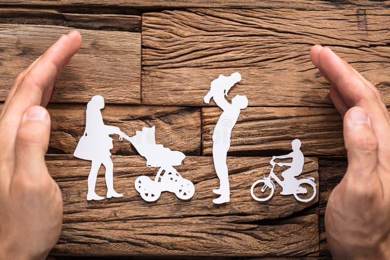 Händer som skyddar papperet för familj` som s ut klipps royaltyfria bilder