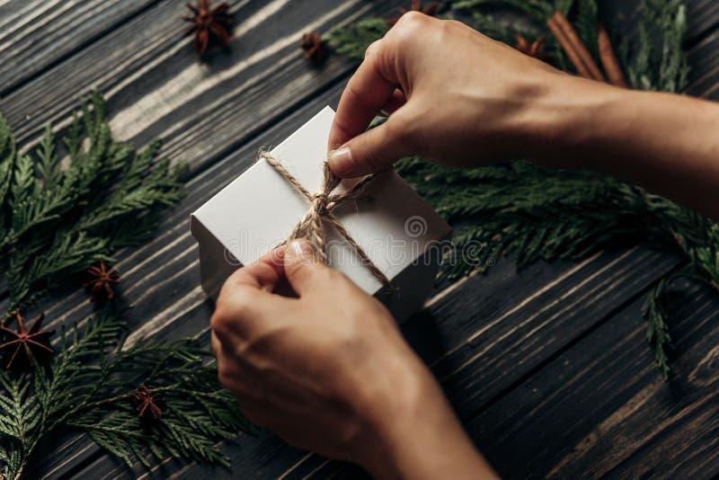 Händer som slår in den enkla närvarande bindande pilbågen för jul på stilfulla rus royaltyfri bild