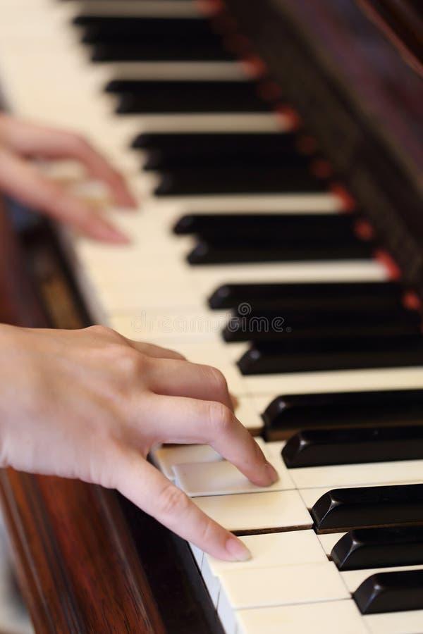 Händer som spelar det klassiska wood pianot arkivbild