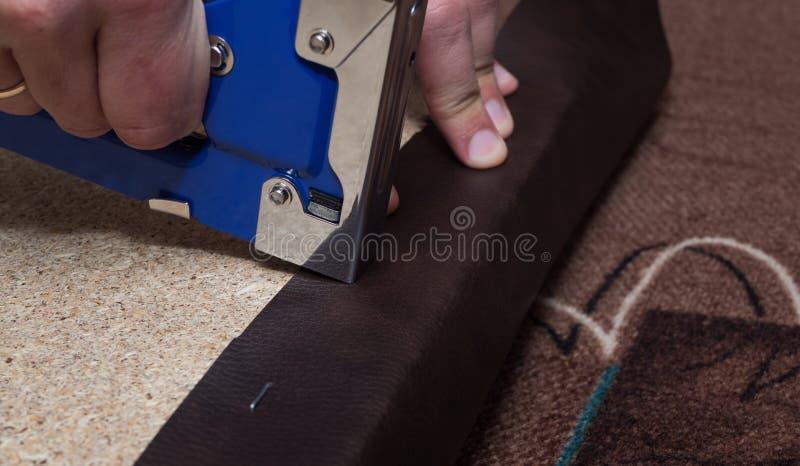 Händer som stoppar pariclebrädet som använder den blåa häftapparaten och brunt läder royaltyfria foton