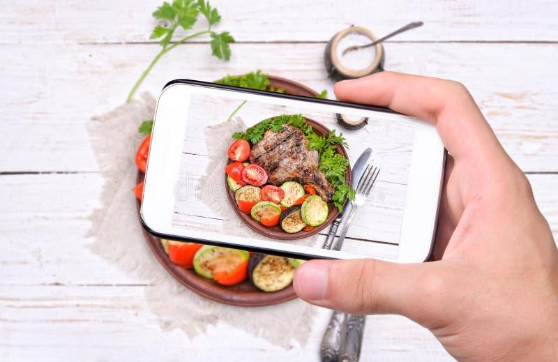 Händer som tar fotoet, grillade stödet med grillade grönsaker med smartphonen royaltyfria bilder