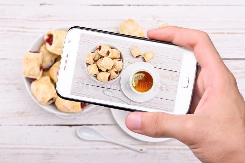 Händer som tar fotokakor med körsbär med smartphonen arkivbilder